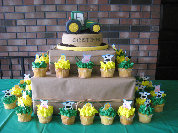 John Deere Tractor Cake on stand with surrounding matching farm cupcakes.