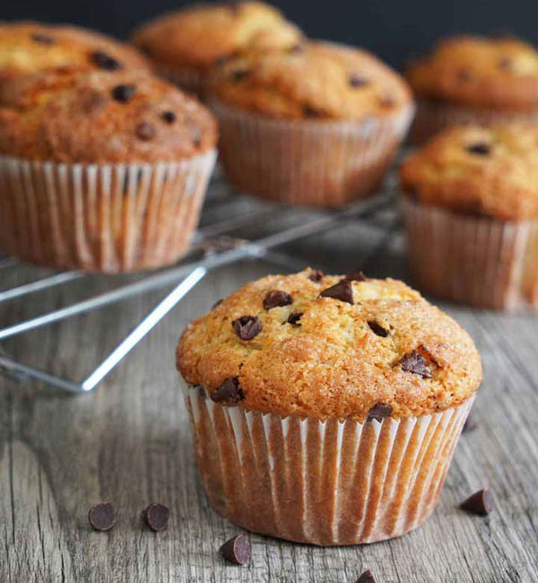 Chocolate Chip Muffin on gray wood board with more muffins on cooling rack in background.