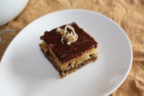 Top view of chocolate chip coconut bar on white plate.