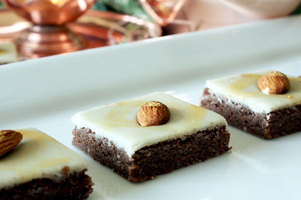 Three chocolate burfi pieces topped with a layer of marzipan and an almond on a white plate.