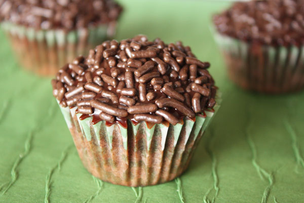 Dark chocolate cupcake with two cupcakes in the background on green surface.