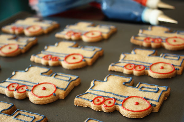Train shaped sugar cookies outlined with red and blue royal icing on a cookie sheet.