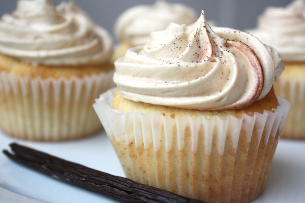 Vanilla bean cupcake with more cupcakes in the background and vanilla bean in the foreground.