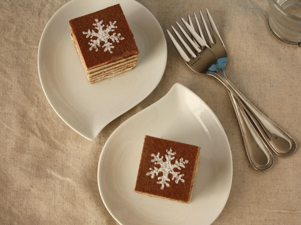 Top view of cinnamon walnut cake slices on two white plates with forks on the side.