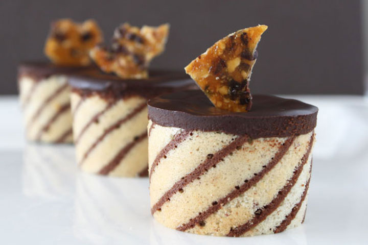Three hazelnut mousse entremets wrapped in striped joconde and topped with hazelnut brittle, lined up diagonally on a white plate.