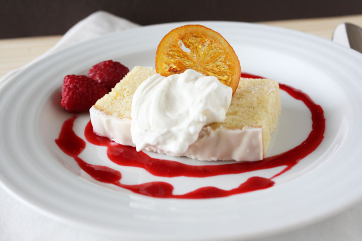 Slice of Meyer lemon poundcake garnished with candied lemon and whipped cream on a white plate decorated with raspberry coulis.