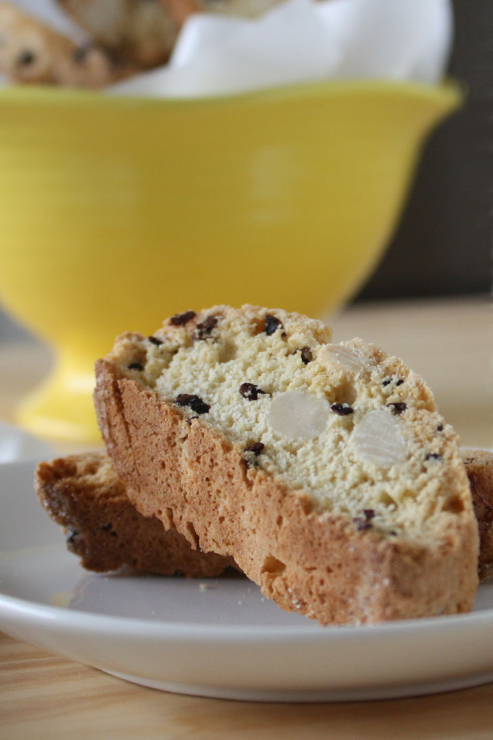 Almondbiscotti withcocoa nibs on a white plate with more biscotti in a yellow bowl in the background.