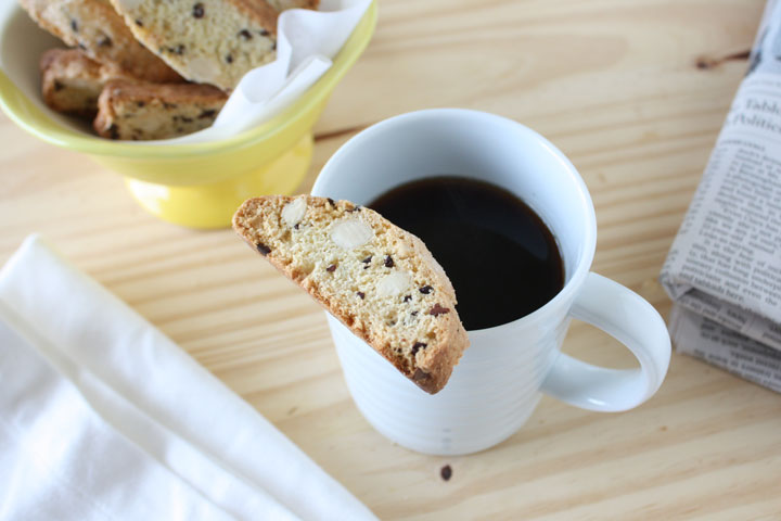 Almondbiscotti withcocoa nibs sitting on top of coffee mug with more biscotti in yellow bowl and newspaper on the side.