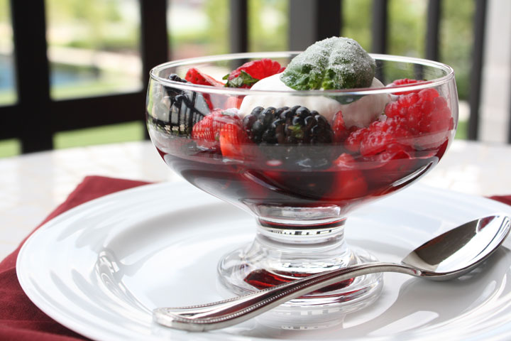 Summer berry salad cocktail with vanilla ice cream and frosted basil leaf in a clear dessert bowl in a white plate with a spoon on the side.