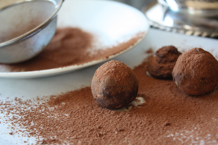Cardamom chocolate truffles being rolled in cocoa powder on a sheet of parchment.