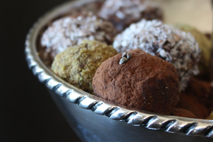 Variety of coated cardamom chocolate truffles in a silver bowl. Pistachio, Cocoa Powder and Coconut coated cardamom truffles.