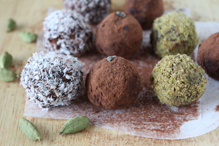 Variety of coated cardamom chocolate truffles on parchment paper with cardamom pods on side. Pistachio, Cocoa Powder and Coconut coated cardamom truffles.