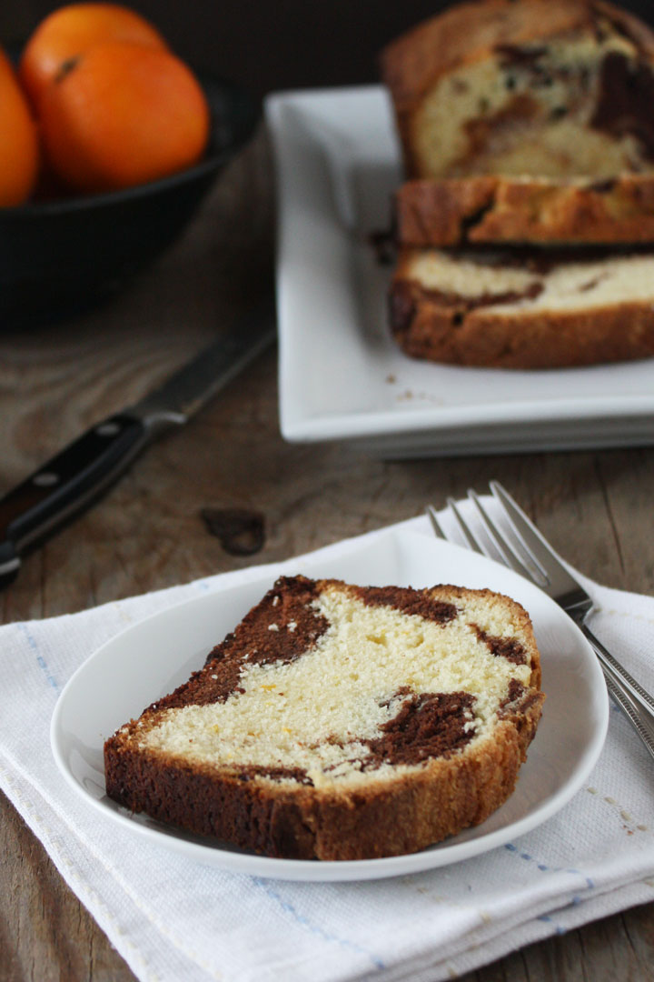 Orange marble pound cake slice with pound cake loaf