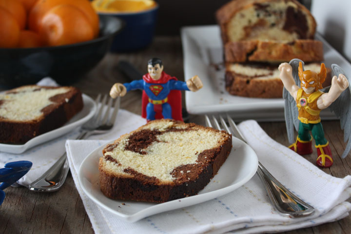 Orange Marble pound cake slice shown with superman and hackman toys on the table.