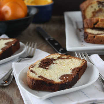 Marble orange point cake slices on white plates with oranges and loaf in background