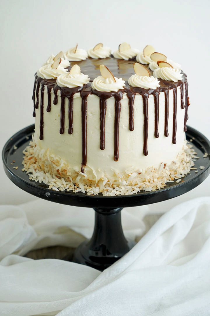 Almond joy cake with ganache drip topping on a black pedestal cake stand and a white background.