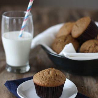 Chocolate chip espresso muffin in plate with glass of milk.