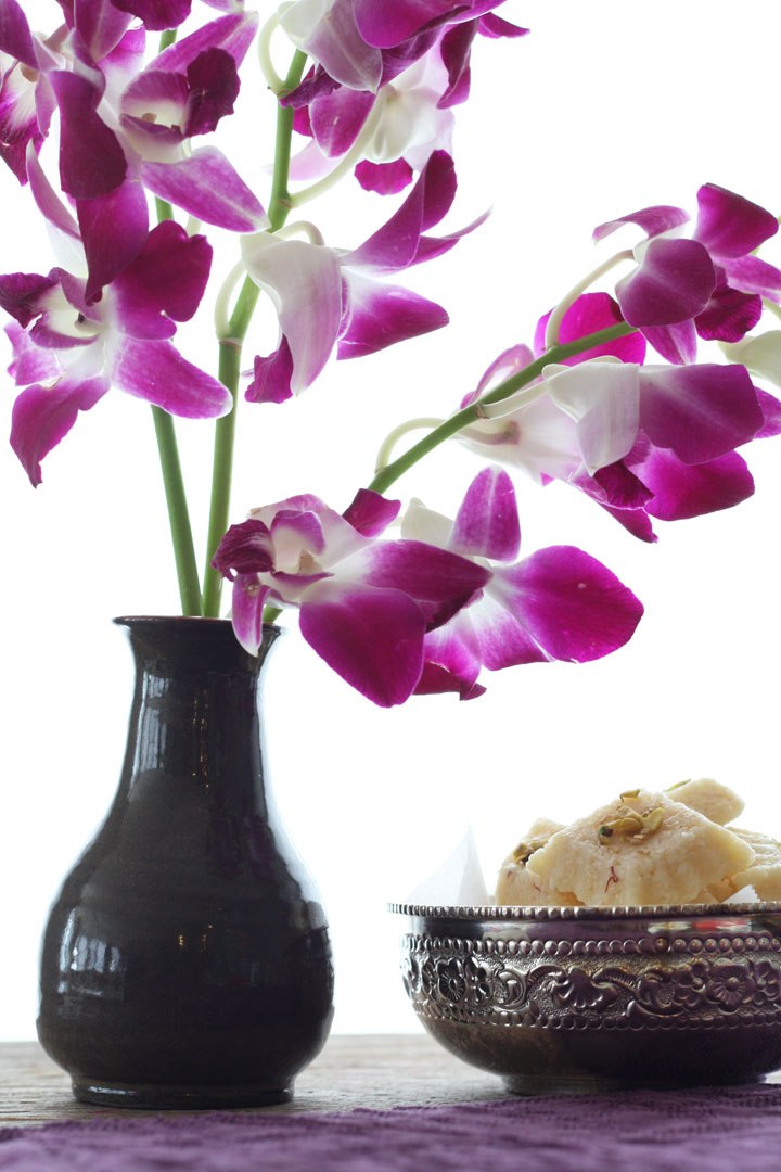 Orchids in a vase next to a bowl of coconut burghs