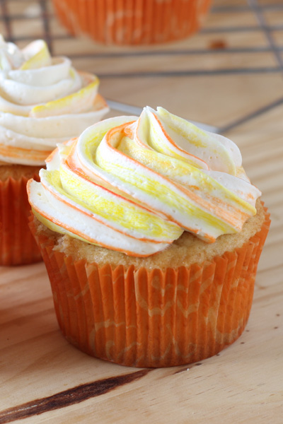 Close up of mango cupcake with Vanilla buttercream swirled on top.