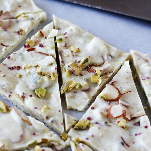 Pistachio white chocolate bark with cardamom and rose cut up on parchment paper.