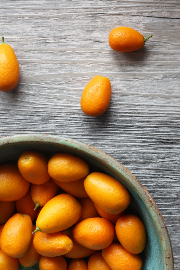 Kumquats in a bowl on wooden surface