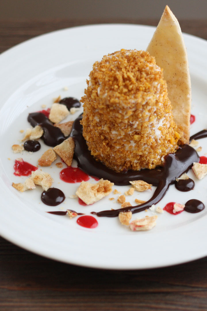 Mexican fried ice cream in a plate with chocolate sauce, raspberry sauce and cinnamon tortilla chips.