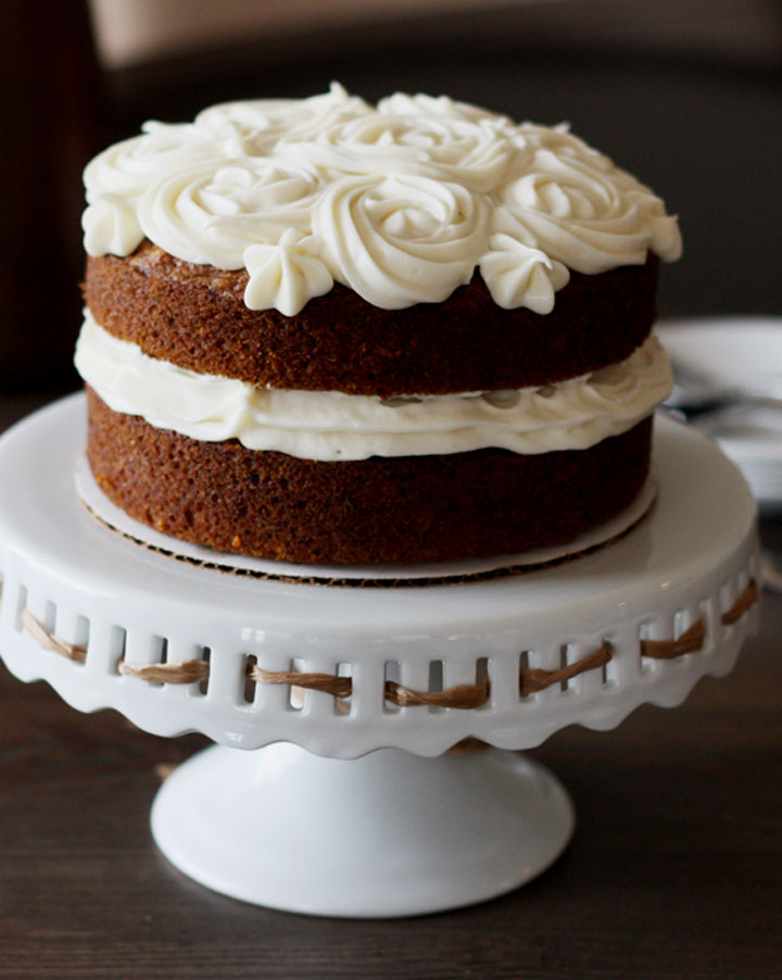 Simple 6 inch carrot cake with cream cheese frosting on a white pedestal stand.