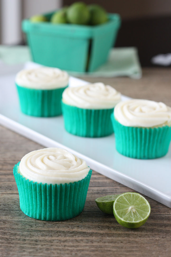 Key lime cupcake with cream cheese frosting in green cupcake wrapper with cupcakes in background and key limes on the side.