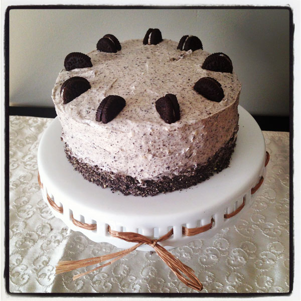 Chocolate Cake with oreo frosting and mini oreos sitting on a white cake pedestal