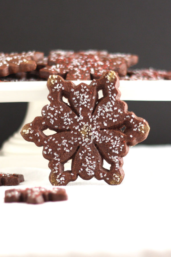 chocolate peppermint snowflake cookie with cookies on pedestal in background