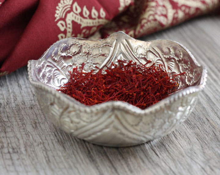 Decorated silver bowl full of saffron strands with red napkin in the background.