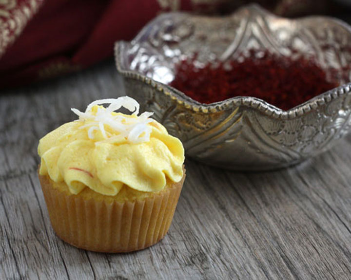 Saffron cupcake with coconut garnish in front of silver bowl full of saffron threads.