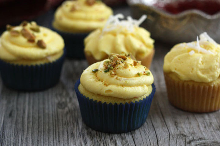 Saffron cupcakes topped with golden saffron buttercream with coconut or pistachio garnishes.
