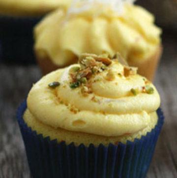 Saffron cupcake with saffron buttercream and pistachio garnish on top.