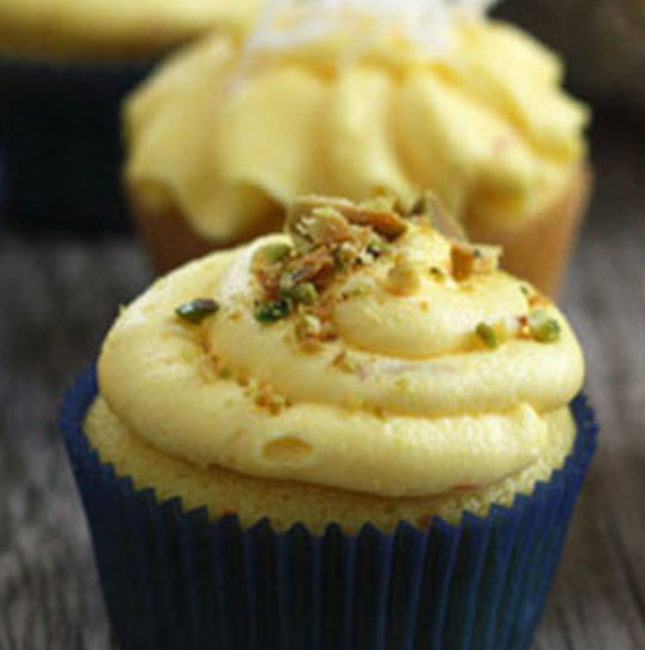 Saffron cupcake with saffron buttercream and pistachio garnish on top.