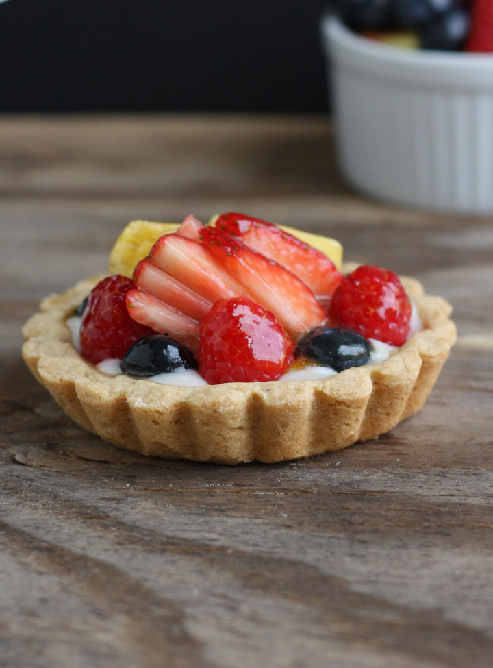Close up of mini fruit tart with strawberries, blueberries and pineapple topped with a shiny glaze.