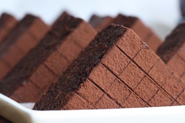 Triangle shaped brownies lined up in a white tray.