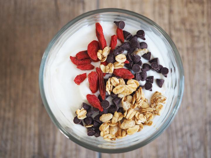 Top view of vanilla yogurt parfait with granola, chocolate chips and goji berries.