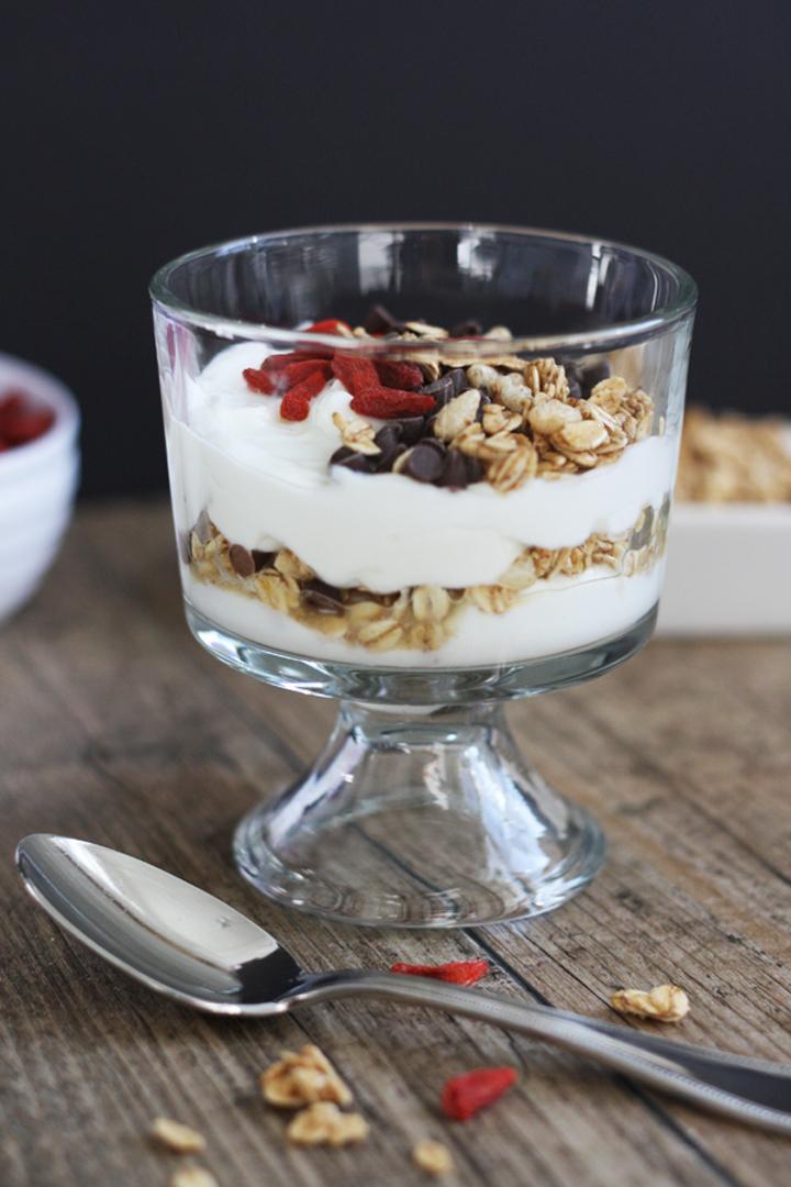 Yogurt parfait with vanilla yogurt, granola, goji berries and chocolate chips in a stemmed dessert glass.