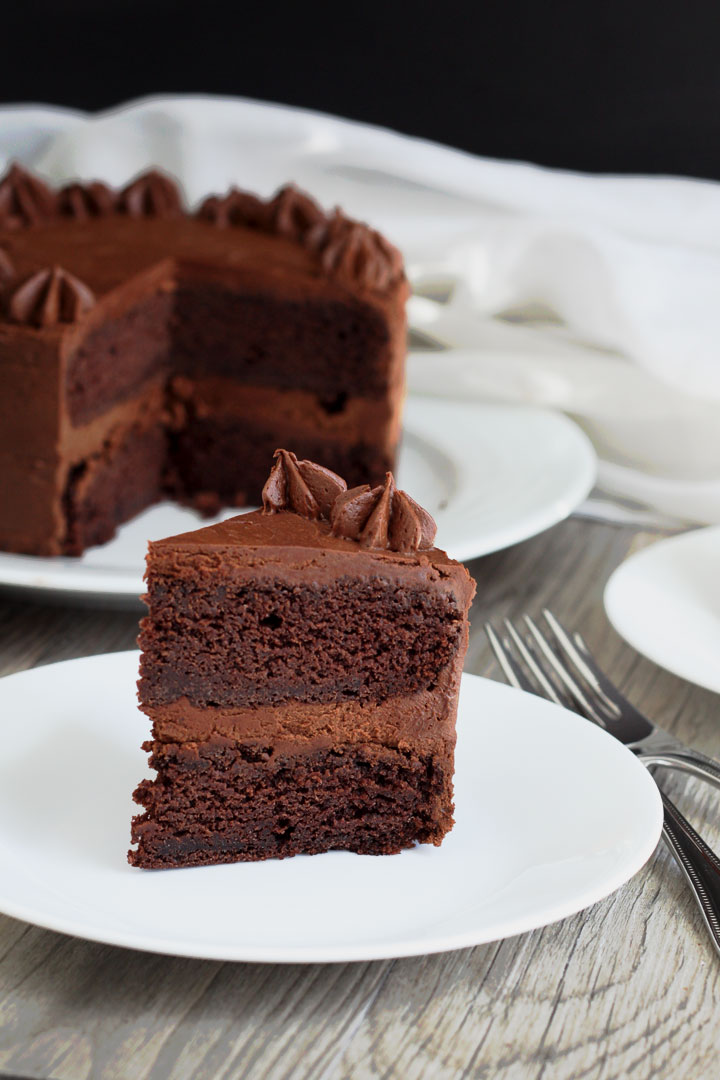 Slice of chocolate cake with fudge frosting in white plate with whole cake in background.