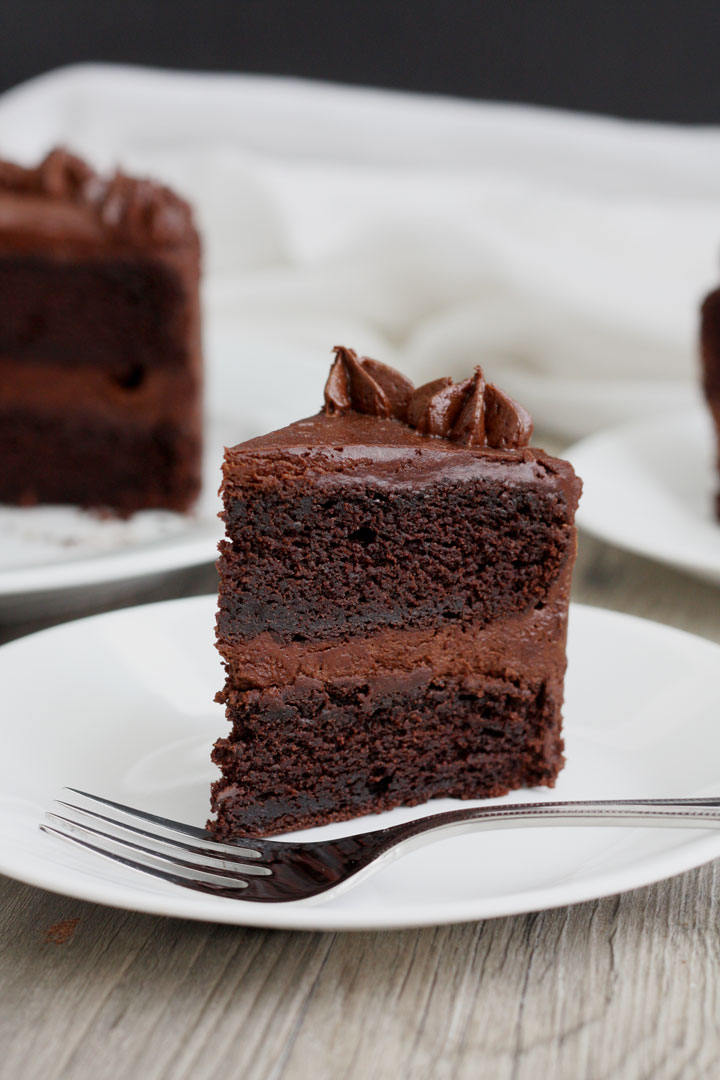 Slice of chocolate cake with fudge frosting in white plate.