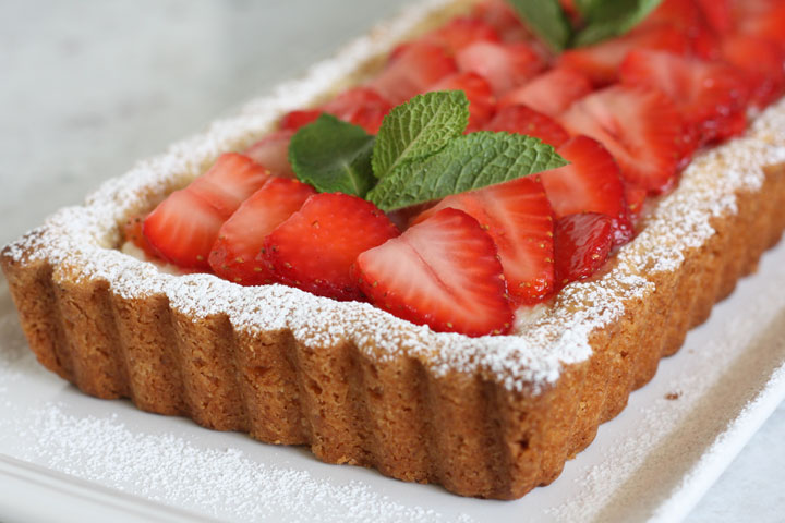 Close up view of one end of the tart filled with mascarpone and topped with strawberries.