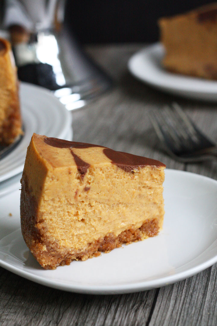 Slice of pumpkin cheesecake with chocolate swirl top in white plate.