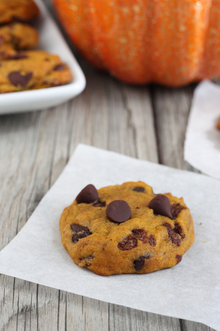 Pumpkin chocolate chip cookie on parchment paper .