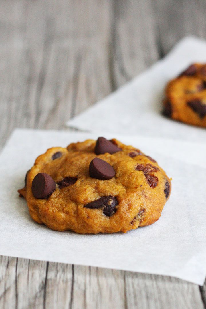 Single pumpkin chocolate chip cookie on parchment paper square.
