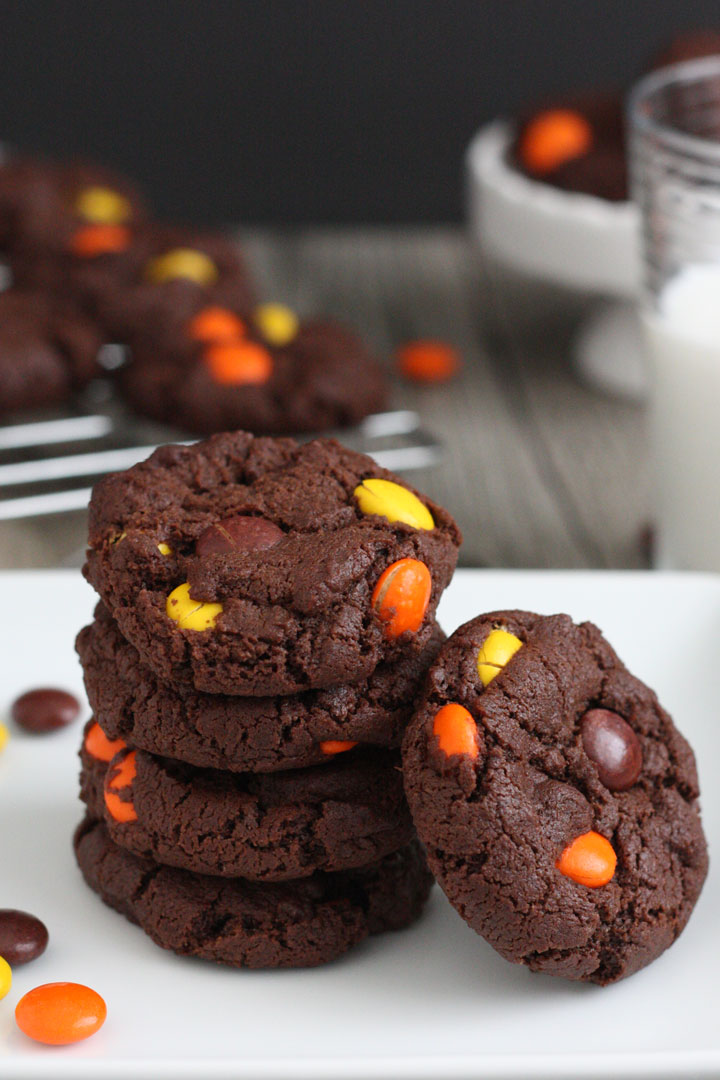 Reese's Pieces double chocolate cookies stacked in a white plate with milk and cookies in background.
