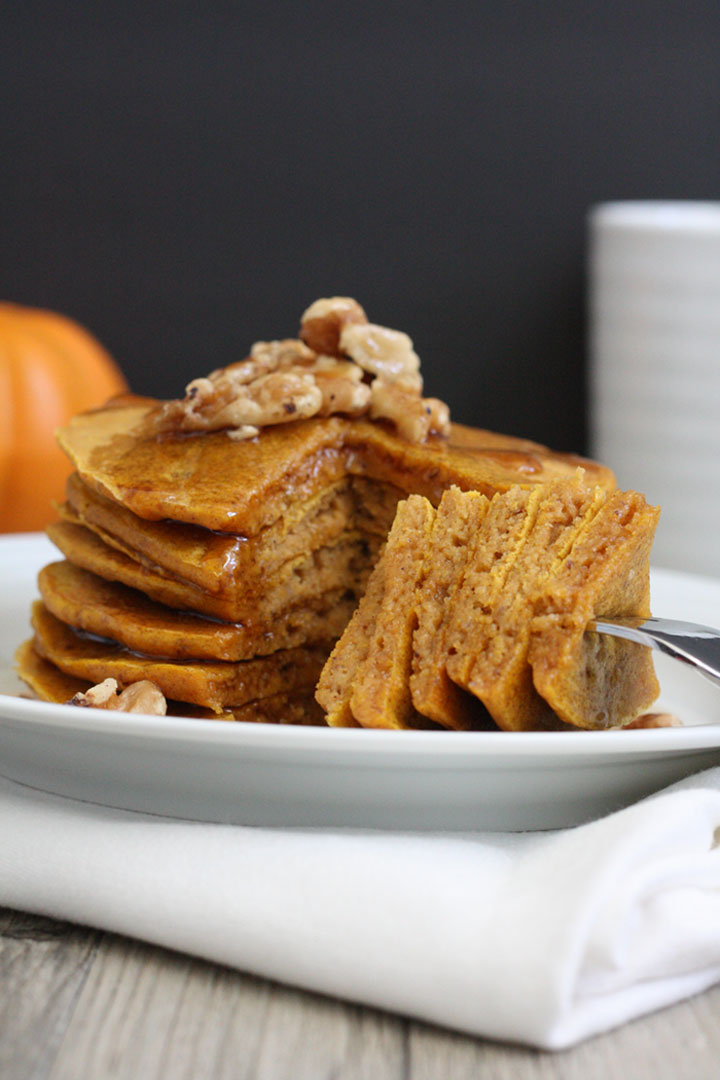 Whole grain pumpkin pancakes stack with pieces cut out onto a fork.