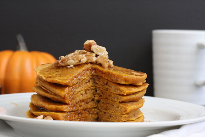 Stack of whole grain pumpkin pancakes with piece cut out.