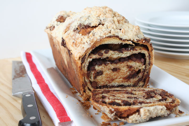 Chocolate Babka loaf with one slice cut off the end in large white platter