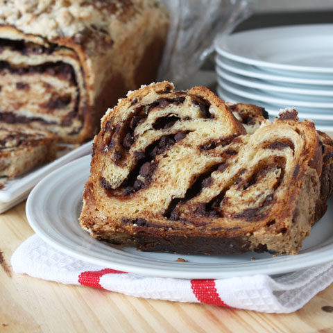 Sliced of chocolate babka on a white plate with chocolate babka loaf in the background.